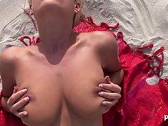 Блондинка с большими сиськами на песке показывает соло прогр...