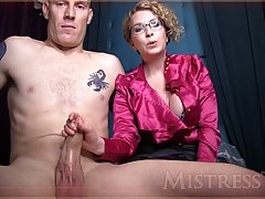 Nasty mature woman with blonde hair and glasses is rubbing dick in front of the camera