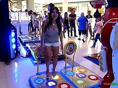 Азиатка во время гулянья по центру показывает свои большие с...