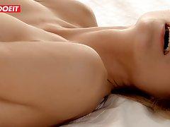Блондинка лежа на спине солирует пальчиками между ног и дово...