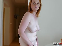 Insatiable, mature redhead is playing with her big tits and ...