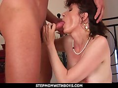Mature brunette is playing with her tits and getting her hai...