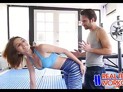 Стройная брюнетка делает себе упражнения на растяжку когда е...